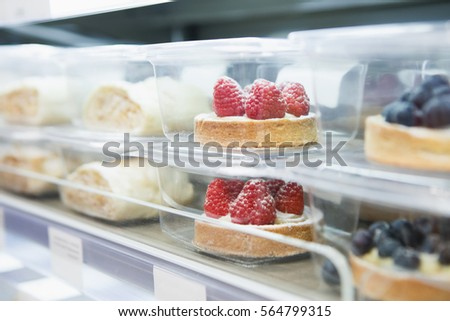 Delicious little cake in refrigitator on shelf packed in plastic container.Fresh sweet pastry food for coffee break.Little cup cakes for dessert.Buy frozen bakery products Royalty-Free Stock Photo #564799315