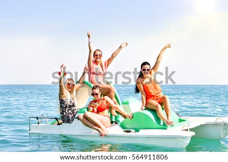 Happy young women having fun raising arms smiling on rental pedalos in blue ocean - Best female friends boat party and sunny  joyful moment together - Concept of summer holiday and teenage friendship  #564911806