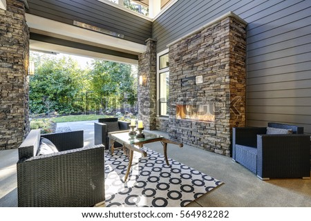 Well designed covered patio boasts stone fireplace, wicker patio chairs facing gorgeous rustic wood coffee table atop white and black geometric rug. Northwest, USA  #564982282