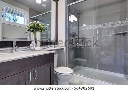 Bright new bathroom interior with glass walk in shower with grey tile surround, brown vanity cabinet topped with white counter and paired with mosaic tile backsplash. Northwest, USA  #564982681
