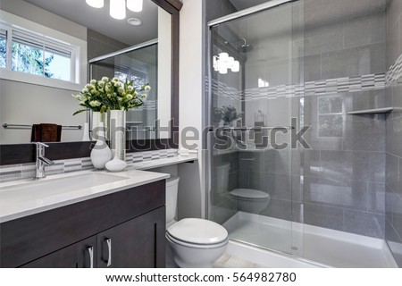 Bright new bathroom interior with glass walk in shower with grey tile surround, brown vanity cabinet topped with white counter and paired with mosaic tile backsplash. Northwest, USA  #564982780