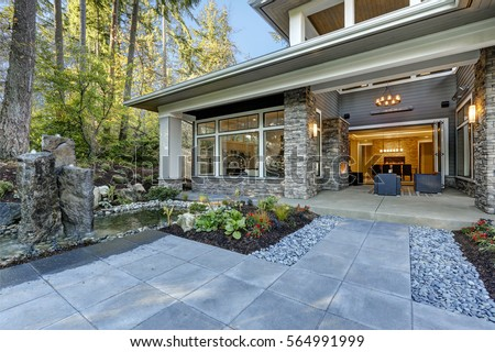 Luxurious new construction home exterior with front patio and perfect landscape design: nice garden pond with stone fountains. Northwest, USA  #564991999