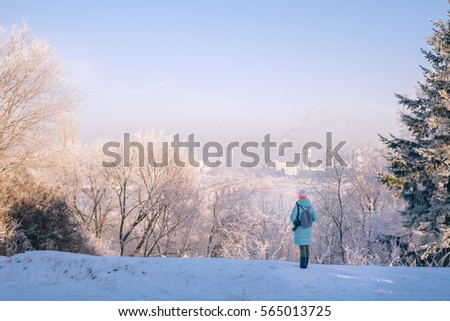 Young woman walking in magic winter city park with cityscape landscape #565013725