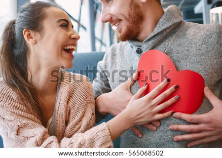 man and woman smiling and holding a large paper heart. Two people in cafe communicate, laughing and enjoying the time spending with each other. Couple in love on a date.  Valentines Day concept #565068502
