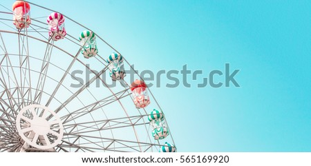 Colorful ferris wheel of the amusement park in the blue sky  background. #565169920