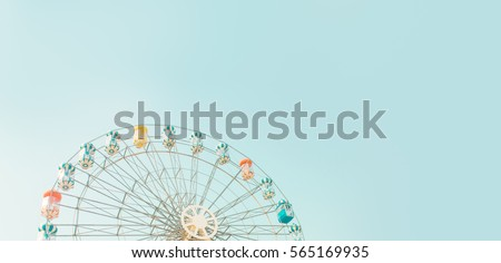 Retro colorful ferris wheel of the amusement park in the blue sky  background. Royalty-Free Stock Photo #565169935