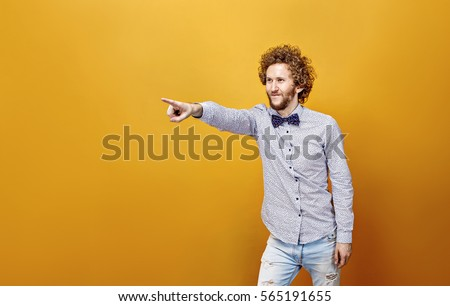 Portrait of happy smiling curly-haired man in bow-tie showing something with finger.Isolate.Yellow background. #565191655