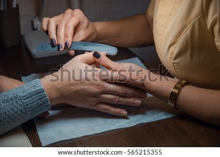 Female makes manicure, fengernails treatment #565215355