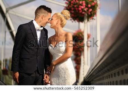 bride and groom posing on a metal bridge #565252309