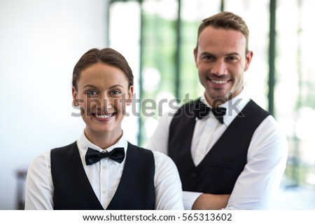 Waiting staff smiling at camera in a commercial kitchen Royalty-Free Stock Photo #565313602