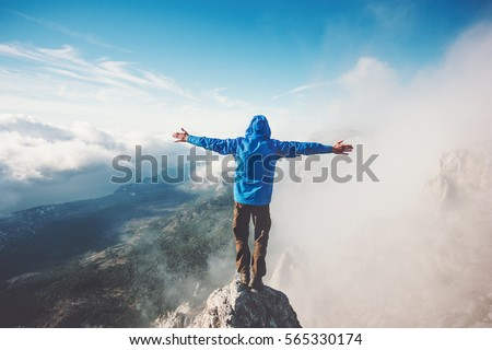 Happy Man on mountain summit enjoying aerial view hands raised over clouds Travel Lifestyle success concept adventure active vacations outdoor freedom emotions Royalty-Free Stock Photo #565330174
