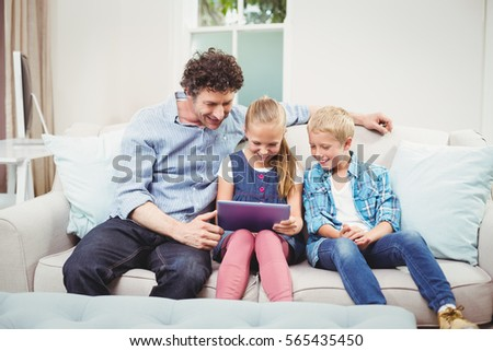 Father with children using digital tablet on sofa at home #565435450