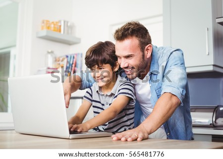 Father and son using laptop on table at home #565481776
