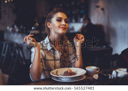 beautiful girl blonde hair and make-up, dine in the restaurant, eating delicious served hot dish, Italian pasta, spices, fine dining, europe, food, Kef, lunch, breakfast and dinner in the cafe Royalty-Free Stock Photo #565527481