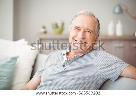 Portrait of happy senior man smiling at home #565569202