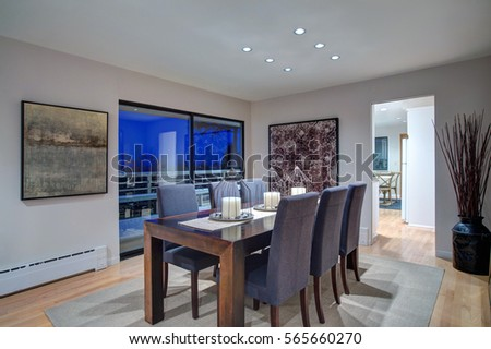 Grey tones dining space is fitted with dark wood dining table with decorative candles on the top and surrounded by upholstered grey dining chairs. Glass doors lead to oversized deck. Northwest, USA