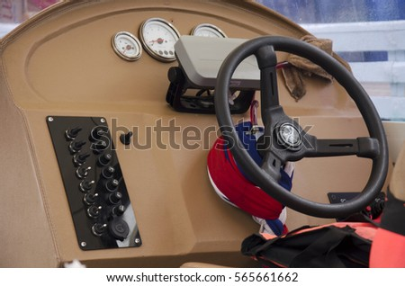 Steering wheel of speed boat and control panel console #565661662