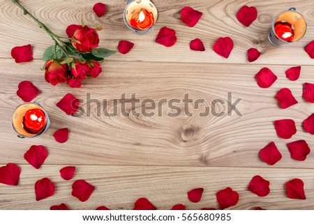 Red fabric rose and rose petals with candle tealights on a wood background #565680985
