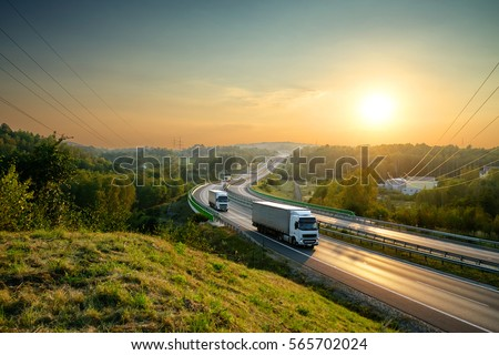 White trucks driving on the highway winding through forested landscape at sunset. #565702024