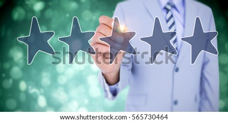 Midsection of businessman writing with marker against blue abstract light spot design #565730464
