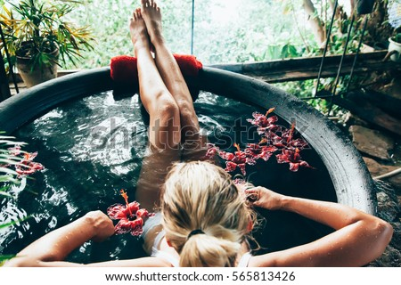 Woman relaxing in round outdoor bath with tropical flowers. Organic skin care in kawa hot bath in luxury spa resort. #565813426