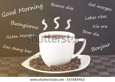 Cup of coffee with beans on a blackboard background with the word good morning written in many different languages. (Toned image with shallow depth of field)