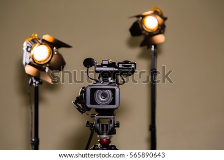 Video camera (camcorder) on a tripod and two halogen spotlights with Fresnel lenses. Shooting an interview. #565890643