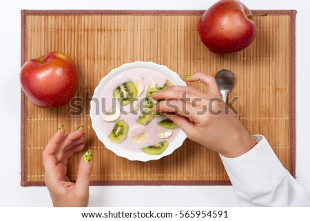 top view of a hand with a kiwi and a plate with yogurt and fruits #565954591