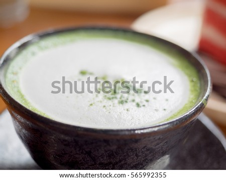 enjoy matcha green tea latte in black ceramic cup on wood table and background of dessert with low contrast effect #565992355