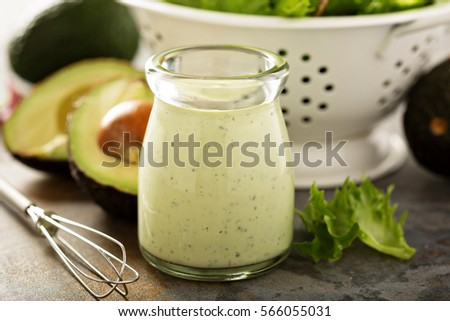 Homemade avocado ranch dressing in a small jar with fresh greens. #566055031
