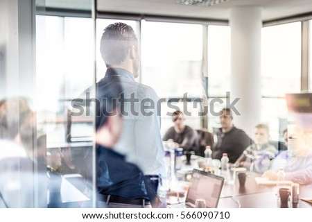 Business man making a presentation at office. Business executive delivering a presentation to his colleagues during meeting or in-house workshop. Rear view. Business and entrepreneurship. Royalty-Free Stock Photo #566090710