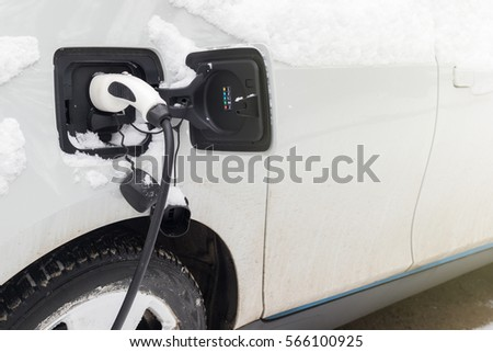 Electric car charging. Car and socket covered by snow in winter time #566100925