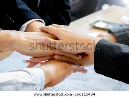 Business teamwork concept with hands of businessmen and businesswomen together above office table #566115484