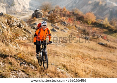 Bike cyclist with red backpack riding single track #566155486