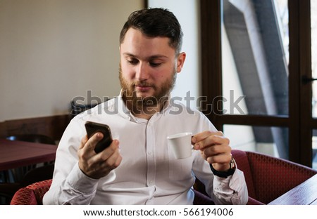 Young happy man sitting in cafe and using phone with cup of coffee  #566194006