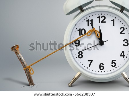 Time on clock stop by nail, delay concept Royalty-Free Stock Photo #566238307