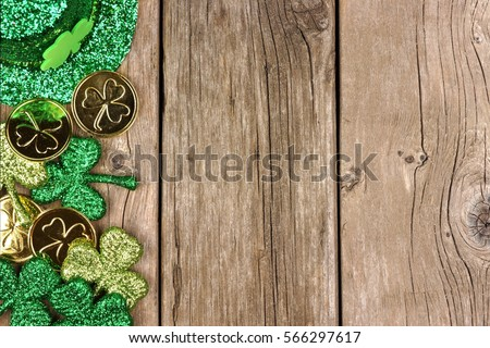 St Patricks Day side border of shamrocks, gold coins and leprechaun hat over rustic wood