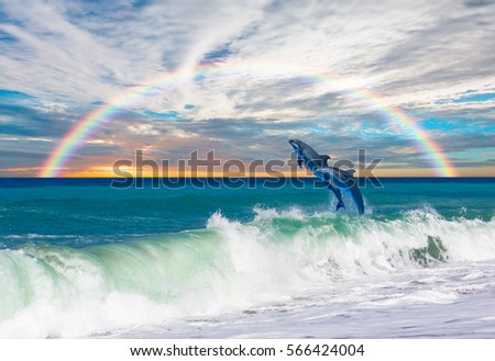 Two happy playful dolphins leaping from sea breaking surfing wave to foam