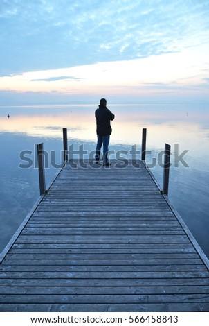 Man on the pier. Lake of Zug, Switzerland #566458843
