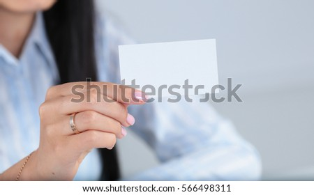 Businesswoman holding blank visit card ,sitting on the desk #566498311
