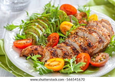 Healthy food. Salad plate with colorful tomatoes, chicken breast and avocado Royalty-Free Stock Photo #566541670