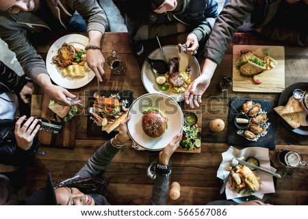 Friends all together at restaurant having meal Royalty-Free Stock Photo #566567086