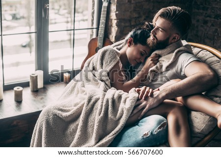 Loving couple. Beautiful young couple covered with blanket resting together while sitting in an armchair at home #566707600