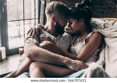 Love is in the air. Young couple sitting face to face and keeping eyes closed while spending time at home together #566707621