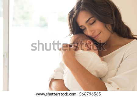 Pretty woman holding a newborn baby in her arms Royalty-Free Stock Photo #566796565