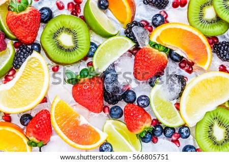 Fresh fruits background.Slices of fresh fruits top view on ice. #566805751