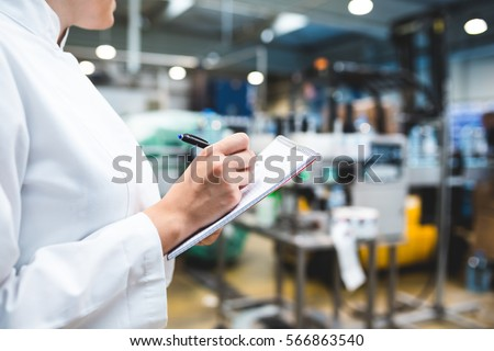 Young happy female worker in factory writing notes about water bottles or gallons before shipment. Inspection quality control. Selective focus on hand. Royalty-Free Stock Photo #566863540