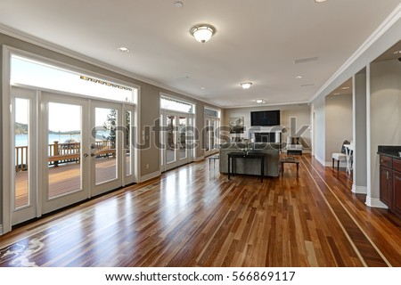 Luxury spacious family room interior with wall of glass doors leading out to spacious deck and facing the lake, polished hardwood floor and cozy sitting area with fireplace . Northwest, USA Royalty-Free Stock Photo #566869117