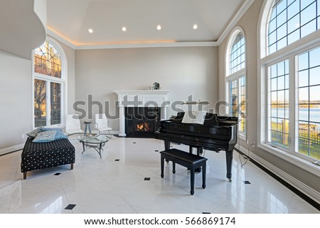 Luxury high ceiling living room features beige ivory walls framing large arched windows, traditional fireplace, black grand piano next to cozy sitting area atop glossy marble floor. Northwest, USA #566869174