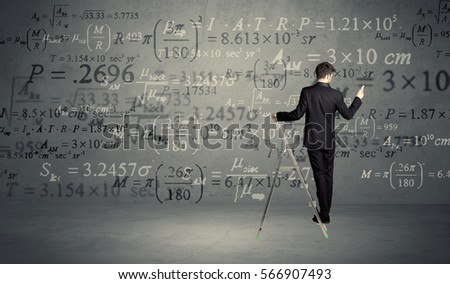 A businessman in elegant suit standing on a small ladder and writing numbers, calculating on grey wall background #566907493
